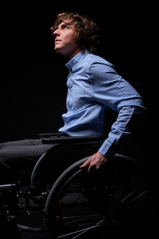 Side view on disabled male sitting on wheelchair and looking up dreaming and thinking about something good, hope for the best