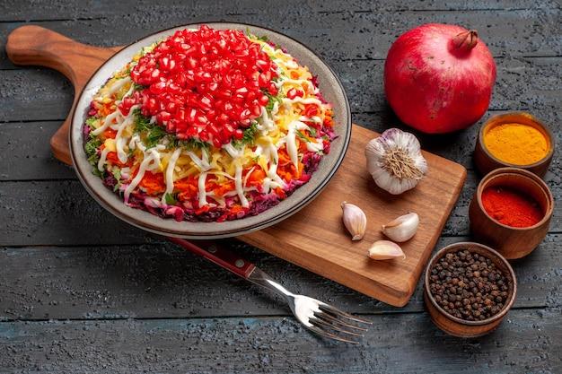 サイドビューディッシュオンボードトップクローズアップビューディッシュオンボードディッシュ食欲をそそるザクロのプレートとニンニクのキッチンボードのさまざまなスパイスフォークとザクロの横