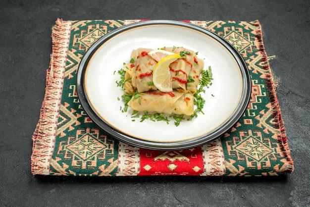 暗いテーブルの上の色とりどりの市松模様のテーブルクロスの上のぬいぐるみキャベツを食欲をそそるテーブルクロスの側面図の皿