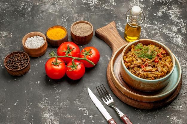 食欲をそそるサヤインゲンのペニセルプレートとトマトの側面図皿トマト、暗いテーブルの上の油とカラフルなスパイスのフォークナイフボトルの横にあるボード上のトマト