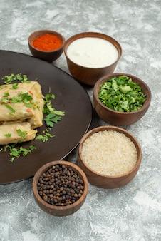 테이블에 향신료 사워 크림 허브 쌀과 후추와 함께 그릇 옆에 박제 양배추의 사워 크림 접시와 사이드 뷰 요리