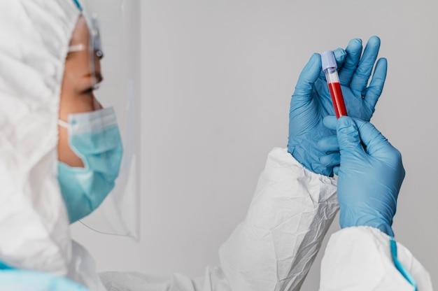 Medico di vista laterale che tiene un campione di sangue