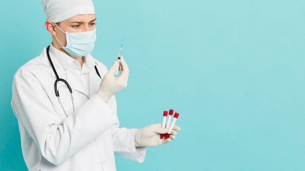 Side view of doctor holding vacutainers and looking at syringe
