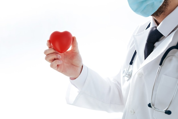 측면보기. 보호 마스크에 의사는 그의 손에 붉은 마음을 보유하고 있습니다. 건강 보호의 개념.