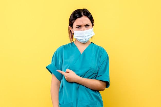 La vista laterale di un medico in maschera incoraggia le persone a indossare la maschera