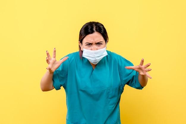 La vista laterale di un medico in maschera parla di una pandemia di coronavirus