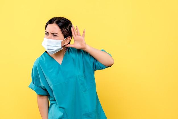 La vista laterale di un medico in maschera ascolta i reclami dei pazienti con covid