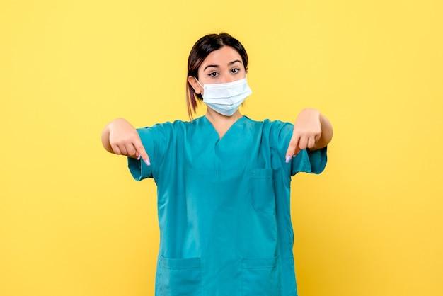 La vista laterale di un medico in maschera punta verso il basso
