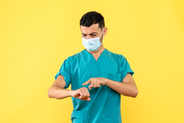 La vista laterale di un dottore in maschera indica la mano destra Foto Gratuite