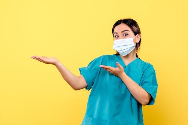 La vista laterale di un medico in maschera parla dell'importanza del lavaggio delle mani