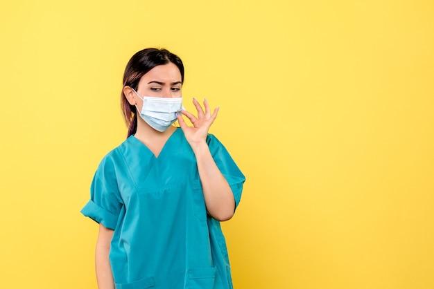 La vista laterale di un medico in maschera parla di indossare la maschera