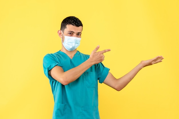 La vista laterale di un medico in maschera invita le persone a lavarsi le mani