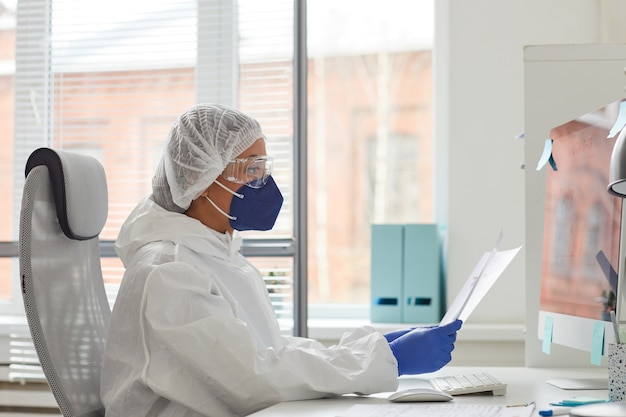 Side view of doctor in protective clothing and in mask sitting at her workplace in front of computer and reading a document at office