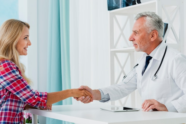 Side view doctor shaking patient hand