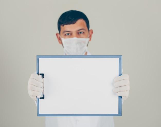 Доктор взгляда со стороны при перчатки смотря и держа держатель бумаги. горизонтальный