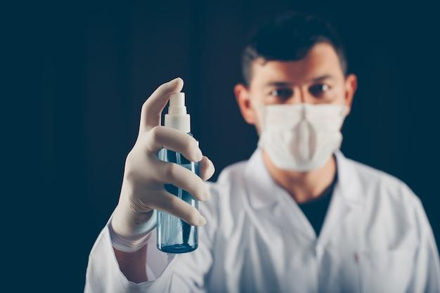 彼の手で医療スプレーを保持しているマスクを持つサイドビュー医師