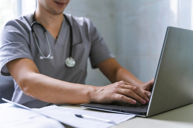 Side view of doctor with stethoscope working on laptop