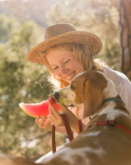 Собака и женщина, вид сбоку, едят ломтик арбуза