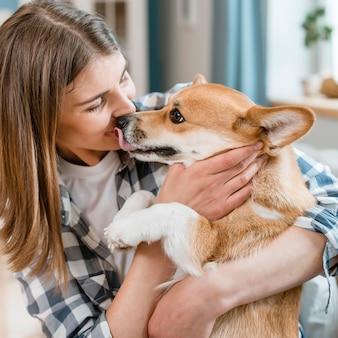 Vista laterale del cane che bacia proprietario femminile