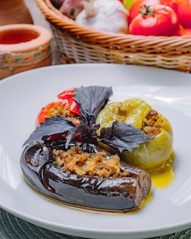 Side view dolma stuffed eggplant tomato bell pepper with ground meat and basil on a plate