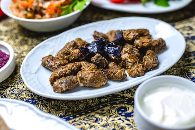 Вид сбоку долма фаршированные виноградными листьями с луком, солью, перцем, базиликом и йогуртом на столе