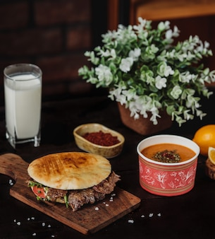Side view of doner kebab in pita bread on a wooden board served with lintel soup and ayran drink on the black table