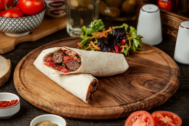 Side view of doner kebab wrapped in lavash with fresh salad on wooden board