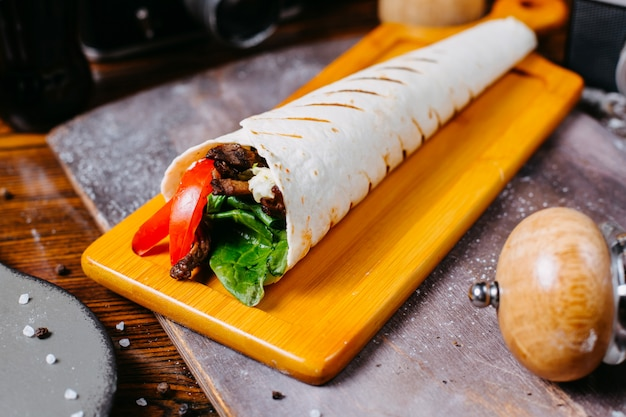 Side view of doner kebab wrapped in lavash on wooden board