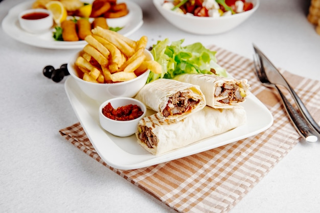 Side view of doner wrapped in lavash and fries on table