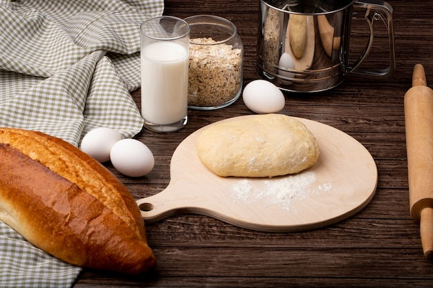Vista laterale di pasta e farina sul tagliere con fiocchi d'avena delle baguette delle uova del latte su fondo di legno