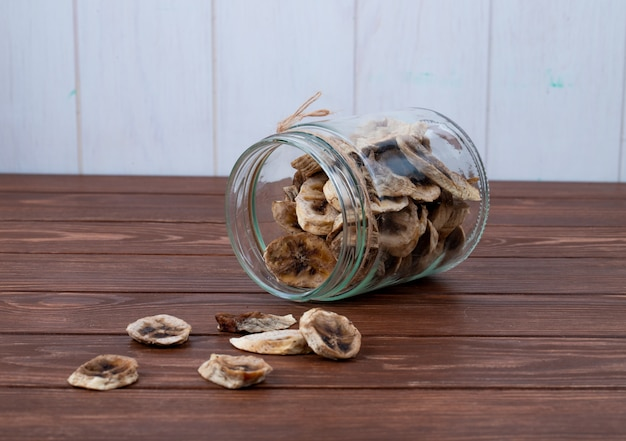 Side view of dried banana chips scattered from a glass jar on wooden background