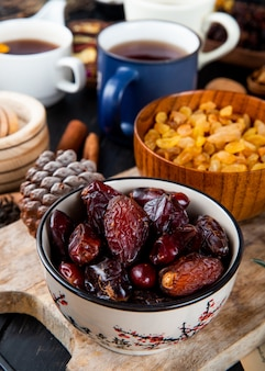 Side view of dried dates in a bowl and yellow raisins in a wood bowl with a mug of tea on the table