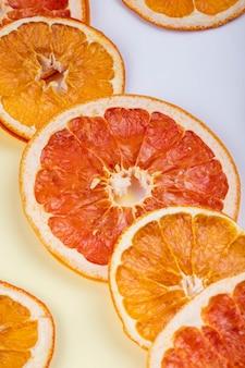 La vista laterale delle fette secche di arancia e di pompelmo ha sistemato su fondo bianco