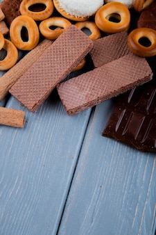 Вид сбоку сухих бубликов с шоколадными вафлями и шоколадом на столе