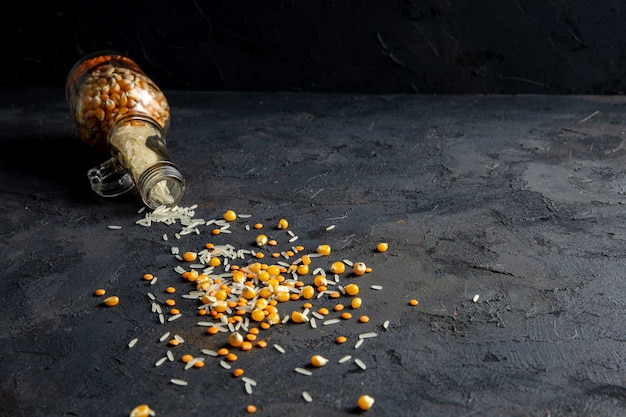 Side view of dry corn seeds and rice scattered from a glass bottle on black