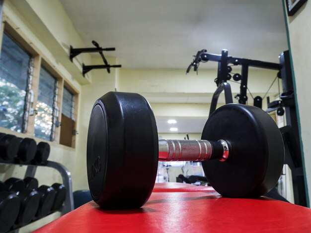 Side view of dumbbell on the red bench in fitness gym