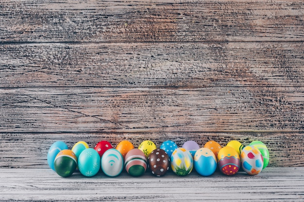 Side view easter eggs on light wooden background.