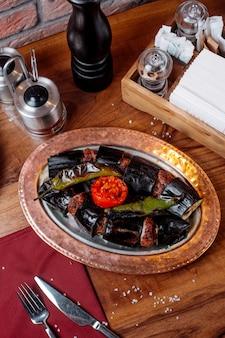Vista laterale del kebab di melanzane con il pomodoro e il peperone verde su una tavola di legno