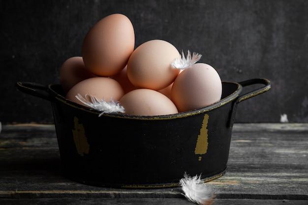 暗い背景の木の羽が付いている鍋の側面図の卵。横型