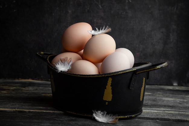 Side view eggs in pot with feathers on dark wooden background. horizontal
