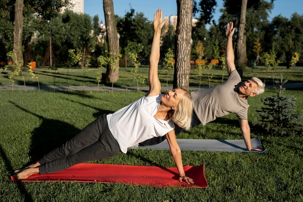 Side view of elder couple doing yoga outdoors