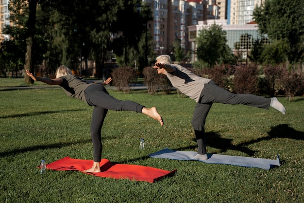 Side view of elder couple practicing yoga outdoors