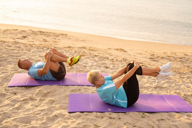 Side view of elder couple working out together on the beach