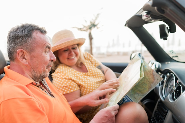 Side view of elder tourist couple on vacation in car with map