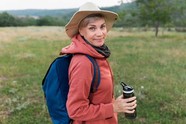 Side view of elder tourist woman with thermos