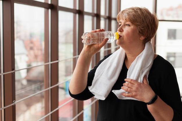 Side view elder woman drinking water