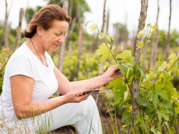 Вид сбоку старшая женщина, стоящая рядом с растением в своем саду
