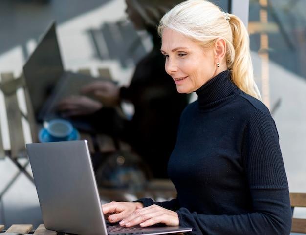 Vista laterale della donna anziana che lavora al computer portatile all'aperto mentre si gusta il caffè