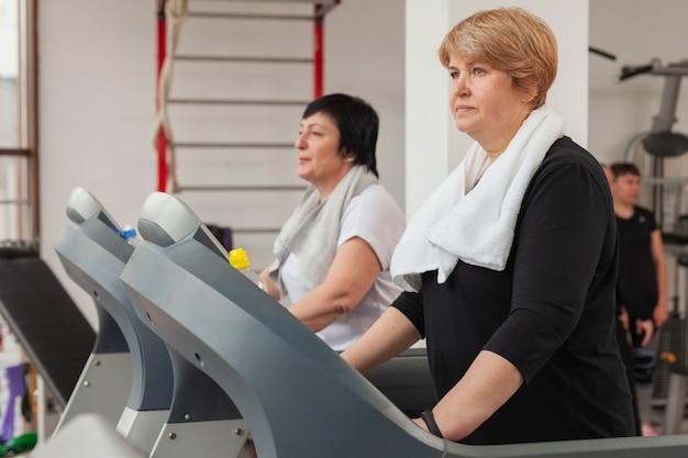 Side view elder women on treadmill