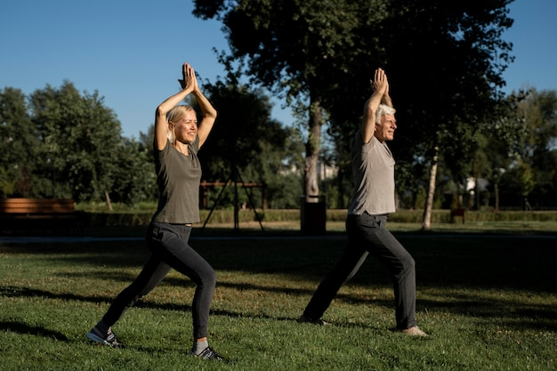 Side view of elderly couple doing yoga outdoors